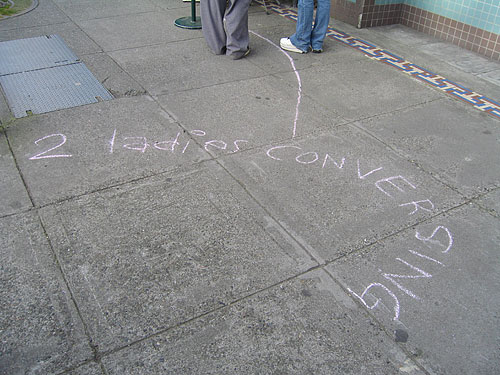 "[chalk on sidewalk: ""2 ladies conversing""]"