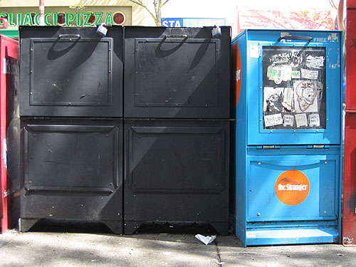 [dull black newspaper boxes]