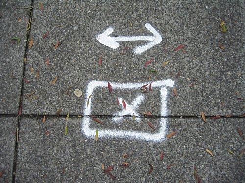 [Spray paint markings on sidewalk]