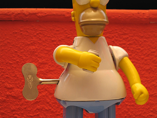 [tin Homer Simpson toy]