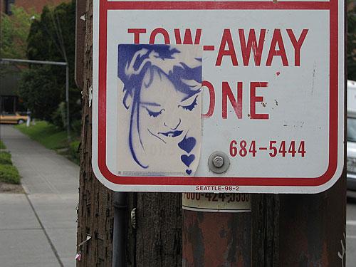 [Stencil girl sticker on street sign]